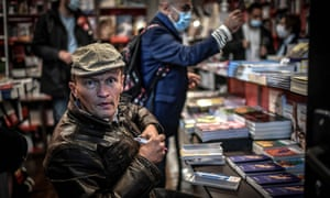 """French writer Sylvain Tesson poses inside the Librairie des Abbesses bookstore as he signs one of his books during the launch of """"Rallumez les feux de nos librairies"""" (Turn back our bookstores' lights) event on November 2, 2020 in Paris, on the fourth day of the second national general lockdown aimed at curbing the spread of Covid-19. Small book traders are forced to shut up shops for a second time this year during what is usually a busy time for retailers in the run-up to the year-end holidays. Owners of bookshops and other specialist outlets complained that the month-long lockdown that came into effect on October 30, 2020 to curb a second wave of infections discriminates against small traders already struggling to survive."""