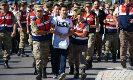 Turkish gendarmes escort a former army special forces officer wearing a 'Hero' T-shirt.