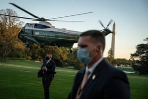 Secret Service agents wearing protective face masks standby as Donald Trump departs from the South Lawn.