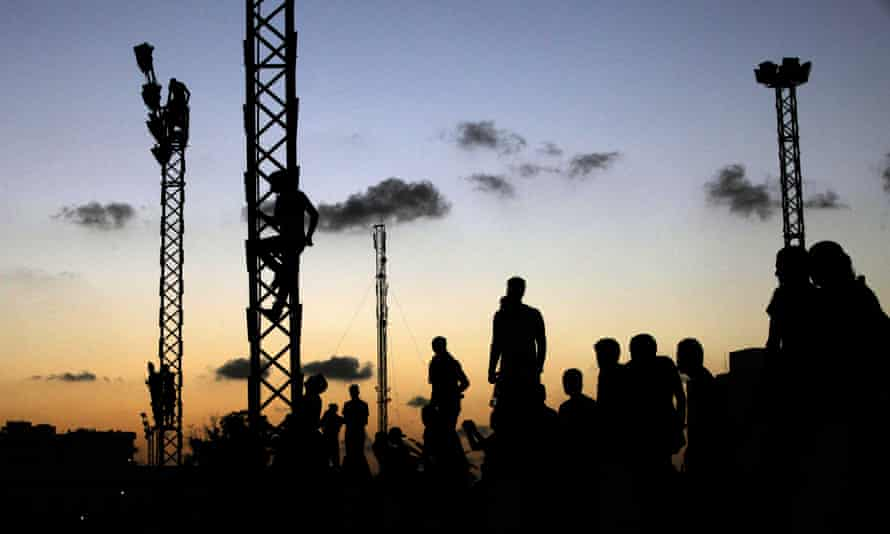 Libyan residents climb up electricity towers to watch a march against Islamic militias, in Benghazi.