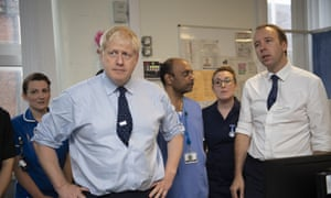 Boris Johnson (left) and Matt Hancock, the health secretary at the North Manchester general hospital, with hospital staff behind them.
