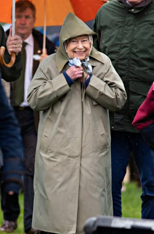Windsor, UK. The Queen smiles through the rain as she watches her horses in the four-year-old hunter class at the Royal Windsor Horse Show
