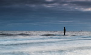 The incoming tide swirls around an Iron Man on Crosby beach, one of 100 statues modelled on and created by Antony Gormley.