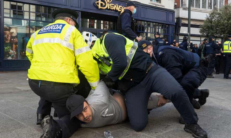 Gardai restrain a protester during an anti-lockdown protest in Dublin city centre