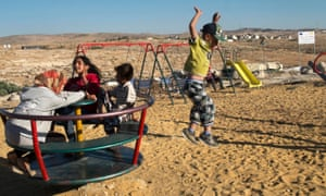 Children in the playground at Khirbet Susiya in the south Hebron Hills with the white walled houses of the Israeli settlement of Susiya visible in the background. Some 37 homes in the Palestinian community are facing the imminent demolition amid efforts by Israeli authorities to move the villagers to another location, moves being opposed by the US and the EU.