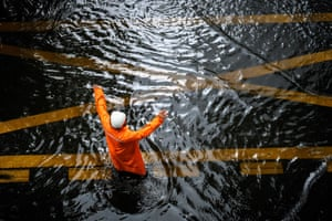 Bangkok: a warden regulates the traffic on a flooded street during a heavy downpour