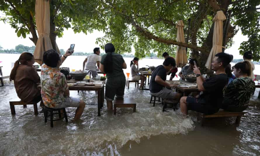 Customers at the Chao Phraya International Cafe in Nonthaburi react as the wake from a passing boat surges through the restaurant.
