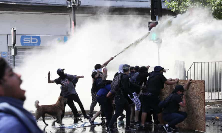 Protests against Chile's government in Santiago<br>Demonstrators take cover as they are sprayed by security forces with a water cannon during a protest against Chile's government in Santiago, Chile November 12, 2019. REUTERS/Ivan Alvarado
