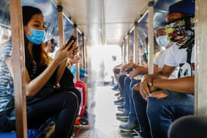 Passengers wearing masks for protection against coronavirus are seated in between plastic barriers to maintain social distancing in a jeepney, in Quezon City, Metro Manila, Philippines, on 3 July, 2020.