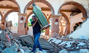 A man carries a St Jude statue from the Inmaculada Concepción church ruins that was built in 1841 and collapsed after an earthquake hit the island in Guayanilla, Puerto Rico, on 7 January.