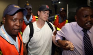 Axed Australian cricket captain Steve Smith is escorted by police officers as he leaves Johannesburg airport.