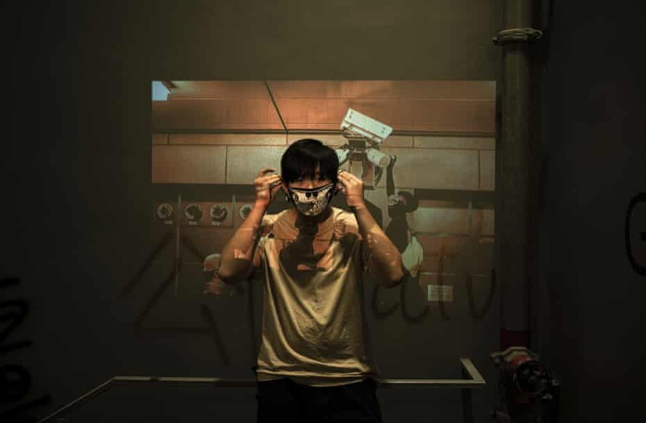 A protester stands in front of a projected image in Hong Kong
