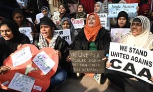 Women protest outside Jamia Millia Islamia University over India's new citizenship law.