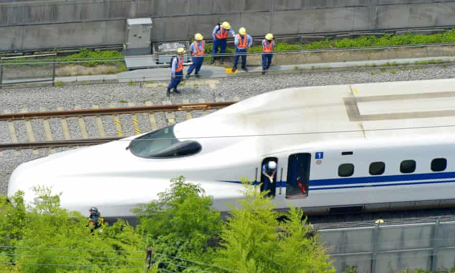 Police officers investigate a Shinkansen bullet train after it made an emergency stop in Odawara.