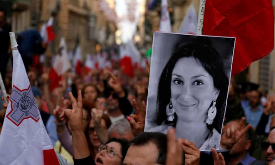 A demonstrator carries a picture of the murdered Maltese journalist Daphne Caruana Galizia in a protest in Valletta, Malta, in April