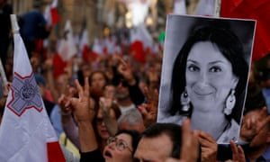 A protester carries a photo of Maltese anti-corruption journalist Daphne Caruana Galizia, who was killed by a car bomb