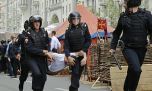 Russian police officers carry off a protester in Tverskaya Street, Moscow.