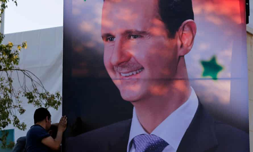 A man helps install a giant banner depicting a portrait of the Syrian president, Bashar al-Assad, during the opening of a flower show in the capital Damascus