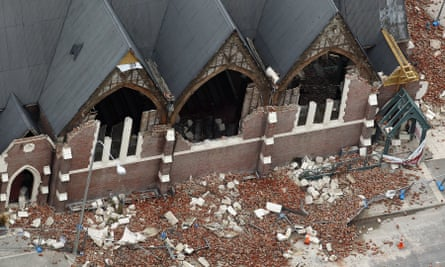 A man rides past a destroyed church in Christchurch, New Zealand.