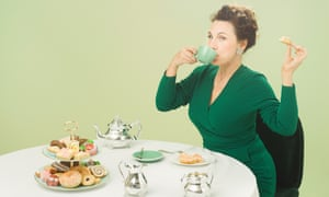 Grace Dent sitting at a table with a cake stand loaded with processed cakes and biscuits