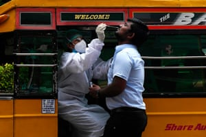 A health worker wearing Personal Protective Equipments (PPE) suit, sits in a share auto-rickshaw as she collects a swab sample from a man to test for the Covid-19 coronavirus, outside a commercial centre in Chennai, India on 12 September, 2020.