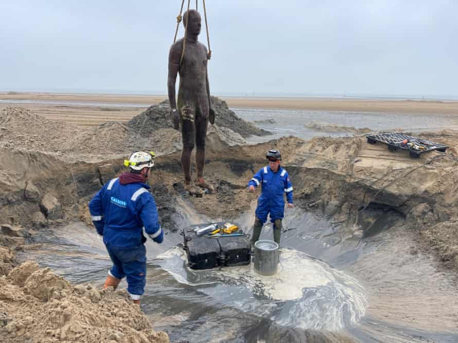 A figure from Gormley's Another Place on Crosby Beach is excavated.
