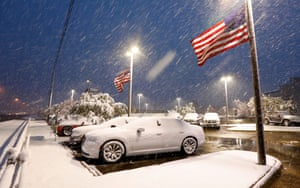 Jackson, MISSUnited states flags flutter as snow falls, blanketing vehicles in a car sales lot. The forecast called for a wintry mix of precipitation across several Deep South states.