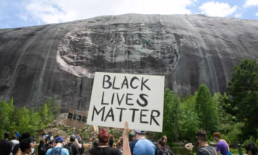 Black Lives Matter Holds Protest Over Recent Police Killings In Stone Mountain, Georgia<br>STONE MOUNTAIN, GA - JUNE 16: A protestor holds a Black Lives Matter sign in front of the Confederate carving in Stone Mountain Park on June 16, 2020 in Stone Mountain, Georgia. The march is to protest confederate monuments and recent police shootings. Stone Mountain Park features a Confederate Memorial carving depicting Stonewall Jackson and Robert E. Lee, President Jefferson Davis. (Photo by Jessica McGowan/Getty Images)