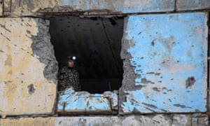 A Ukrainian rescuer stands inside a damaged flat after Russia-backed separatists shelled Avdiivka.