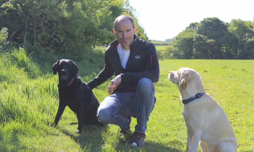 Andrew Cotter posing with his two dogs, Olive and Mabel, in a field