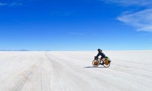 Laura Bingham, raffigurata in bicicletta attraverso un paesaggio innevato in un giorno di cielo blu. Ha pedalato attraverso il Sud America, sopravvivendo puramente alla gentilezza degli estranei