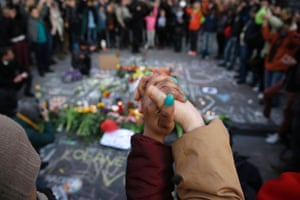 People stand hand in hand in tribute to victims at a makeshift memorial in front of the stock exchange at the Place de la Bourse