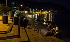 Men transport containers filled with gasoline in the bay of Rio Caribe, in the eastern state of Sucre, Venezuela