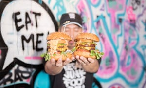 Employee holds up two vegan burgers in front of a colourful mural that says Eat Me! at Vegan Junk Food Bar in Amsterdam, the Netherlands.