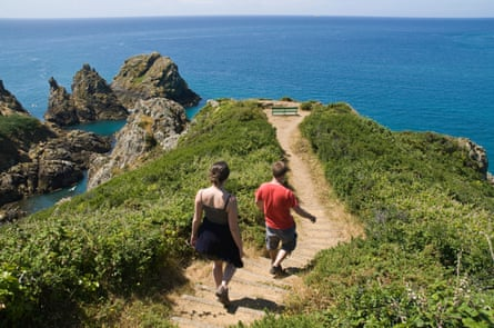 Young tourist couple footpath Pea stacks Les Tas de Pois and rocky headland, ST MARTIN GUERNSEY