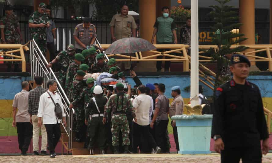Indonesian police and military carry Wiranto to a helicopter after he was stabbed