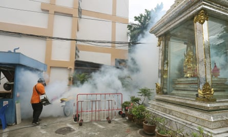 A Thai health official sprays chemicals to kill mosquitoes in the Sathon district of Bangkok, Thailand
