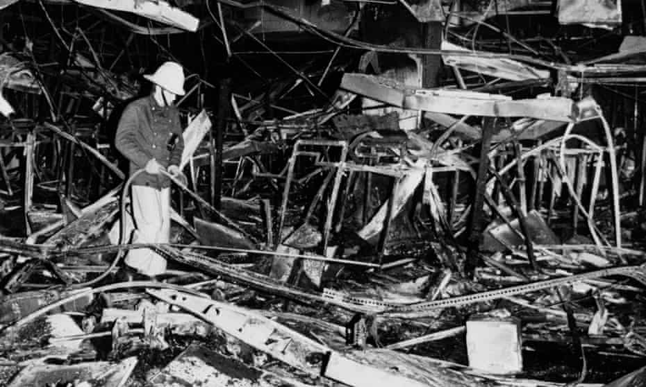 A fireman hoses down the remains of one of the three branches of Debenhams that were set alight as part of the 1987 protest against fur.