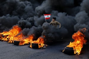 An anti-government demonstrator jumps over tyres set on fire to block a main highway during a protest in the town of Jal el-Dib, Lebanon