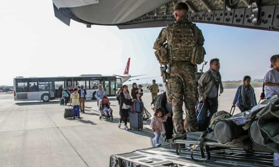 UK citizens and dual nationals get on to a military plane at Kabul airport, Afghanistan, on Monday.