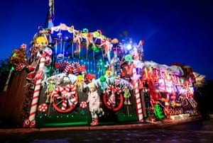 Avaani Podder stands outside the home of Rod and May Proctor, who have covered the building in candy-cane-themed Christmas decorations in Garforth, Yorkshire