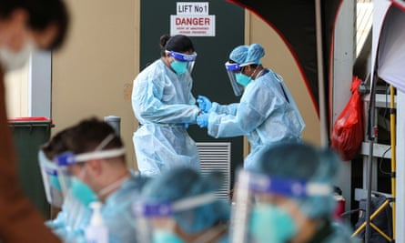 Medical personnel in personal protective equipment are seen at a pop-up testing centre
