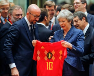 Charles Michel, the Belgian prime minister, handing a football shirt to Theresa May at the opening of the EU summit.