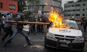 Protestors burn a police car during the global protests in Guerrero, Mexico.