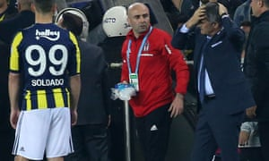 Besiktas head coach Senol Gunes holds his head after being hit by an object during the Turkish Cup semi-final second leg against Fenerbahçe. The match was abandoned.