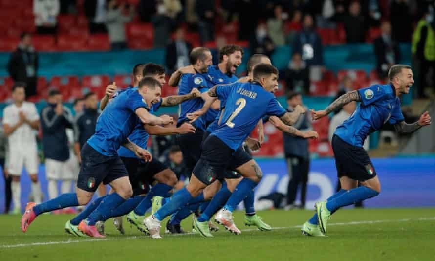Italy's players celebrate as Jorginho's penalty defeats Unai Simón to seal victory.