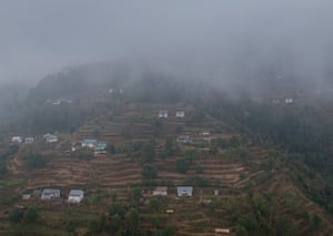 Aerial shot of small houses lost in mist in mountainous landscape