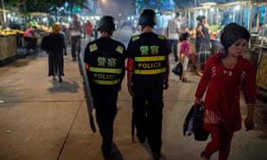 Police patrol a night food market in China's Xinjiang Uighur Autonomous Region.