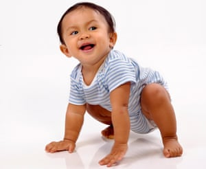 Baby in stripy blue babygrow, crawling and grinning and looking over her shoulder