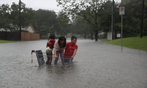 A family evacuate their home after flooding from Hurricane Harvey, Houston, Texas, 27 August